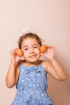 Uśmiechnięte dziecko trzyma dwa jajka
