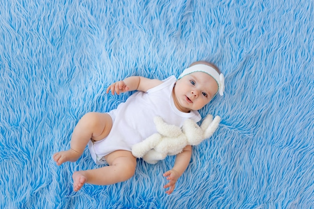 Uśmiechnięte dziecko w białym body leży na niebieskim tle futra z zabawką