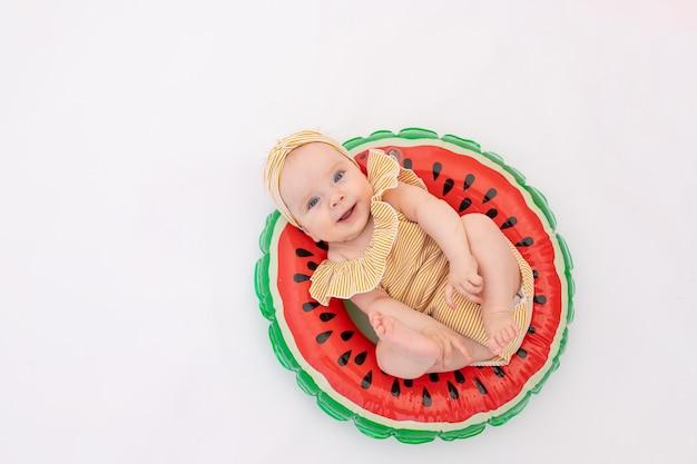 Uśmiechnięte dziecko w kostiumie kąpielowym z kółeczkiem w kształcie arbuza leży.