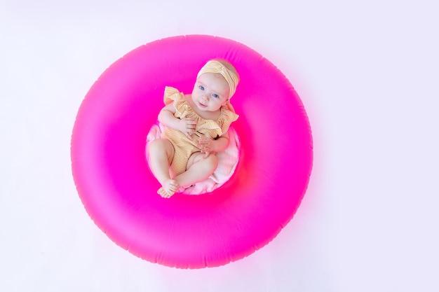 Uśmiechnięte dziecko w kostiumie kąpielowym z różowym kółkiem do pływania leży.