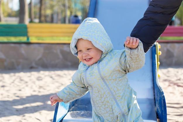 Uśmiechnięte dziecko w niebieskim kombinezonie jeździ na zjeżdżalni. rodzinny styl życia na świeżym powietrzu