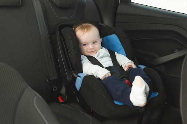 Uśmiechnięte dziecko w wieku 6 miesięcy w foteliku samochodowym