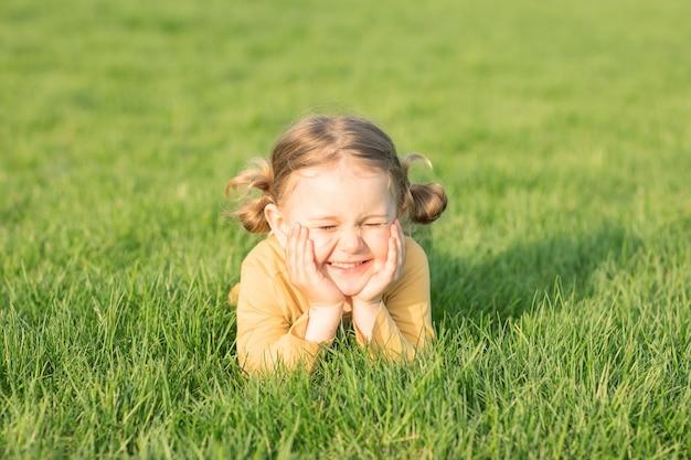 Uśmiechnięte dziecko zamknij oczy leżące na słonecznej zielonej trawie, aby się zrelaksować ciesz się naturą w tle trawy