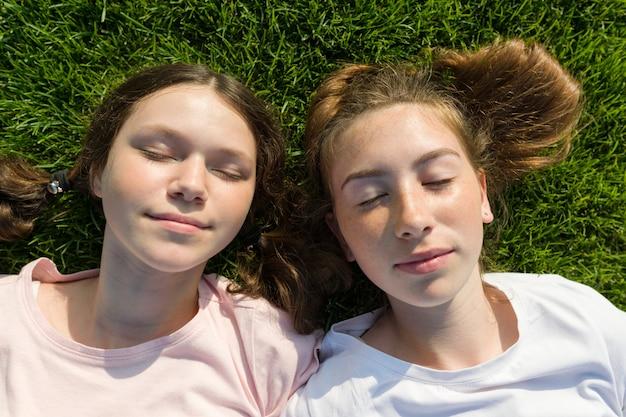 Uśmiechnięte dziewczyny kłama na zielonej trawie z zamkniętymi oczami.