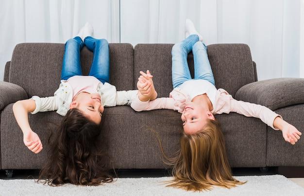 Uśmiechnięte dziewczyny leżące na kanapie do góry nogami trzymając się za rękę w salonie