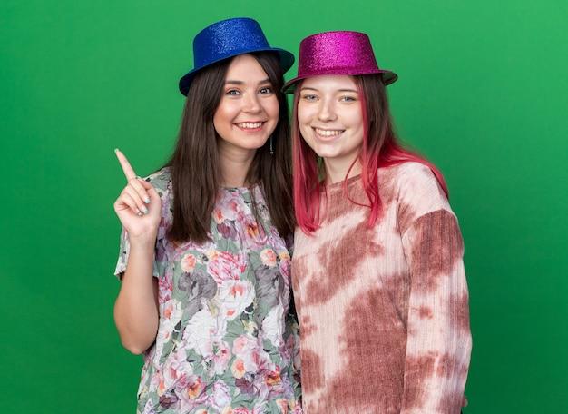Uśmiechnięte dziewczyny noszące czapki imprezowe z boku izolowane na zielonej ścianie