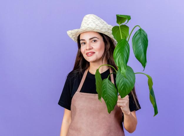 Uśmiechnięte dziewczyny piękne ogrodnik w mundurze na sobie kapelusz ogrodniczy gospodarstwa roślin na białym tle na niebiesko