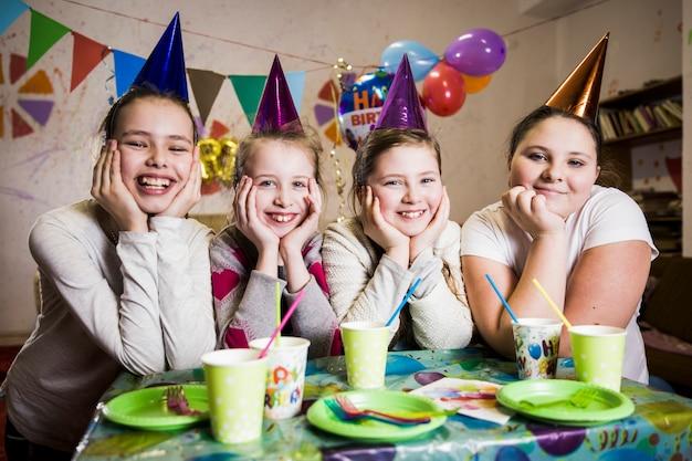 Uśmiechnięte dziewczyny przy stołem na przyjęciu urodzinowym