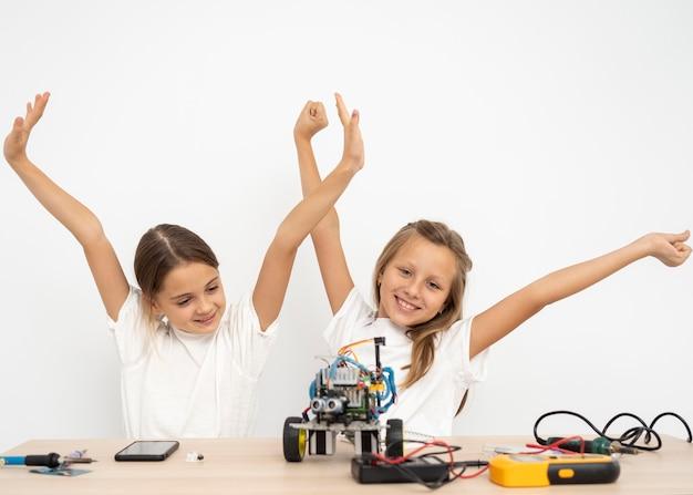 Uśmiechnięte dziewczyny robią eksperymenty naukowe