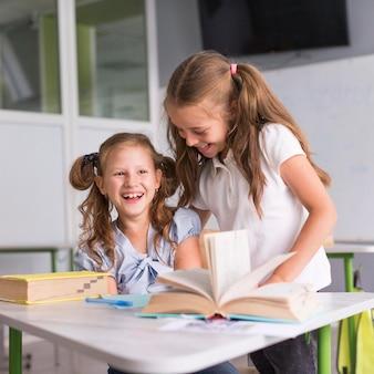 Uśmiechnięte dziewczyny rozmawiają w klasie