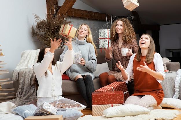 Uśmiechnięte dziewczyny rzucające w powietrze prezenty świąteczne