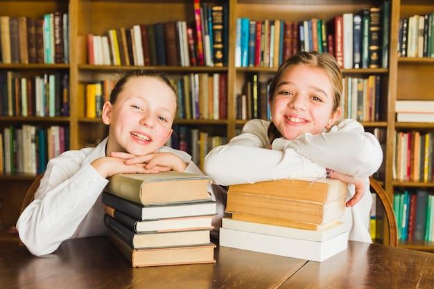 Uśmiechnięte dziewczyny siedzi z stosami książek