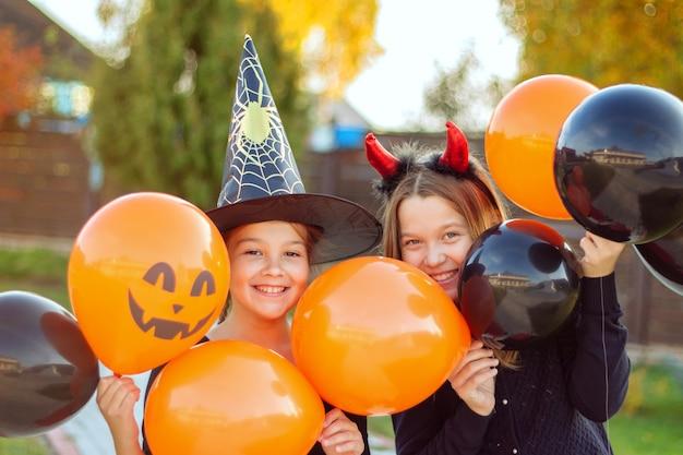 Uśmiechnięte dziewczyny w kostiumach na halloween, trzymające na zewnątrz pomarańczowe i czarne balony, dobrze się bawią, spotykając halloween.