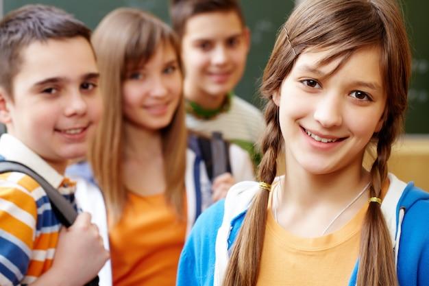 Uśmiechnięte dziewczyny z kolegami za nią