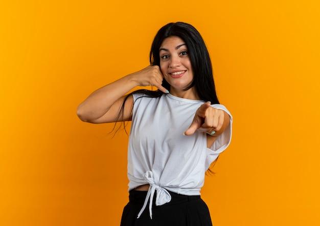 Uśmiechnięte gesty młodej dziewczyny kaukaskiej dzwonią do mnie i wskazuje