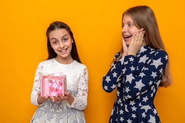 Uśmiechnięte kładące ręce na policzkach dwie małe dziewczynki trzymające prezent