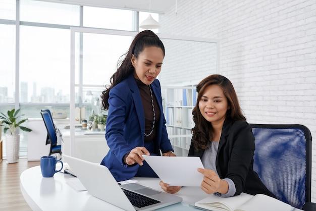 Uśmiechnięte kobiety biznesu omawiają dokument z poleceniem dyrektora generalnego firmy