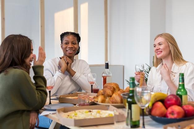 Uśmiechnięte kobiety jedzą razem