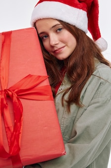 Uśmiechnięte kobiety noszące pudełko z prezentem santa hat. wysokiej jakości zdjęcie