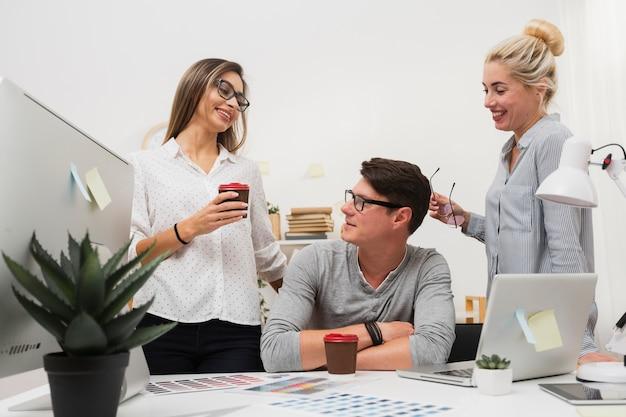 Uśmiechnięte kobiety opowiada z mężczyzna przy biurem