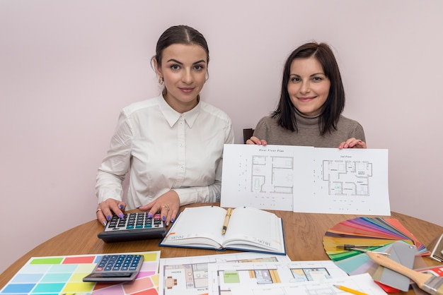 Uśmiechnięte kobiety pokazano plan domu w biurze