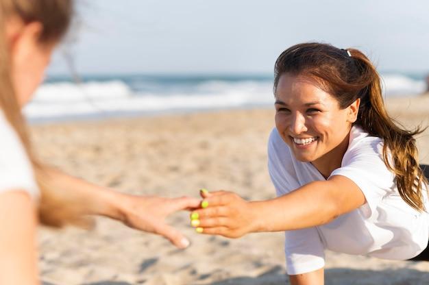 Uśmiechnięte kobiety pomagają sobie nawzajem podczas ćwiczeń na plaży