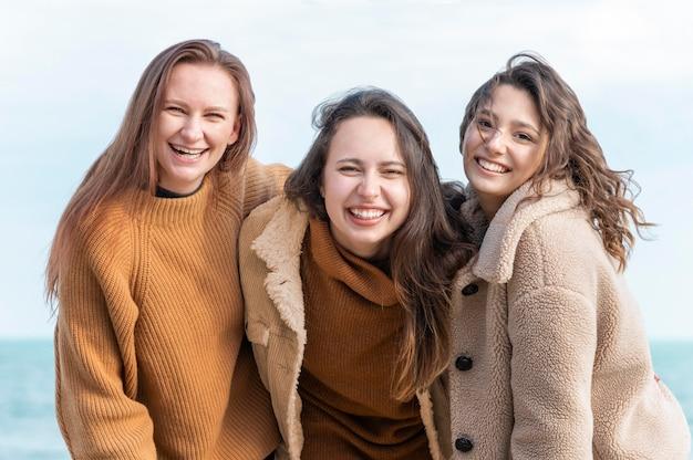 Uśmiechnięte kobiety pozują razem nad morzem