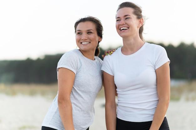 Uśmiechnięte kobiety pozują razem podczas ćwiczeń na plaży