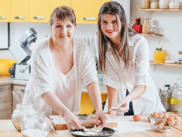 Uśmiechnięte kobiety pozują w rodzinnej kuchni