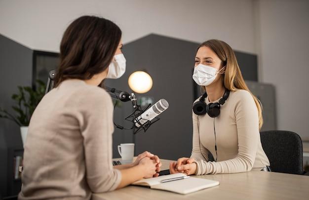 Uśmiechnięte kobiety robią radio w maskach medycznych