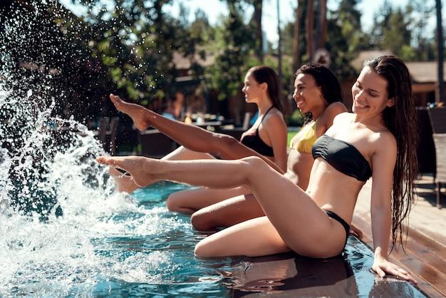 Uśmiechnięte kobiety siedzą przy basenie