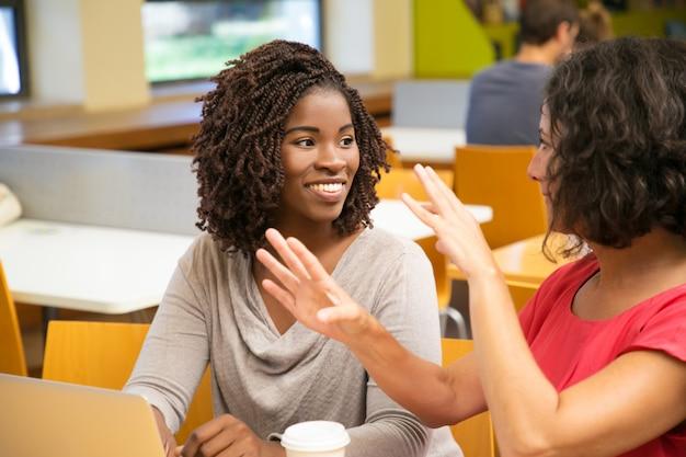 Uśmiechnięte kobiety siedzi przy stołem i używa laptop