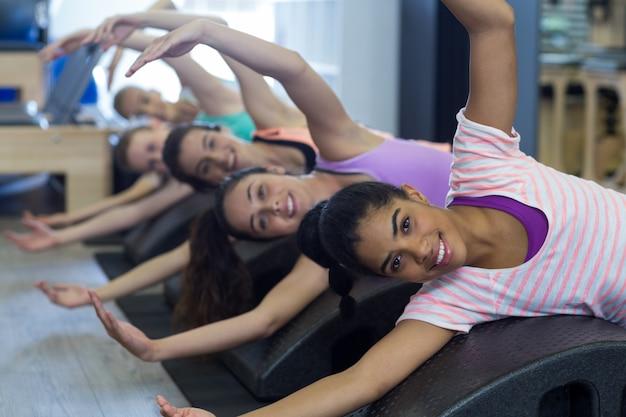 Uśmiechnięte kobiety sprawne ćwiczenia na lufie łuku