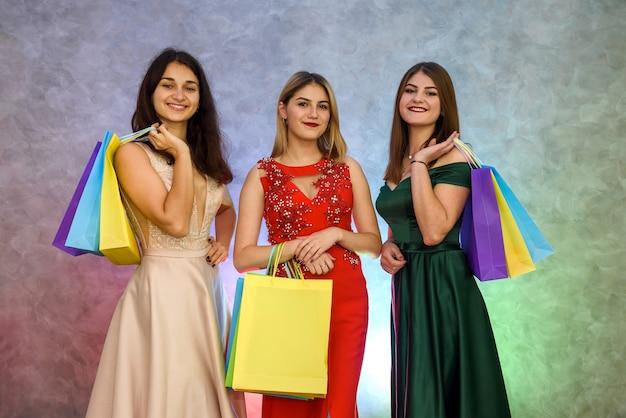 Uśmiechnięte kobiety w eleganckich sukniach pozują z torbami na prezenty w studio. prezenty świąteczne