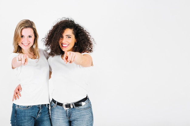 Uśmiechnięte kobiety wskazuje przy kamerą