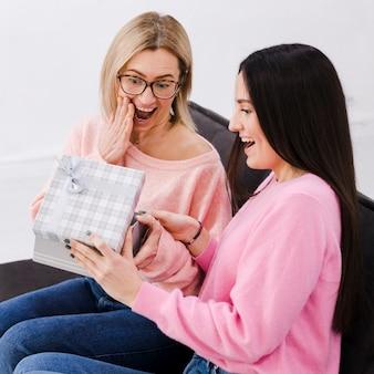 Uśmiechnięte kobiety wymieniające się prezentami