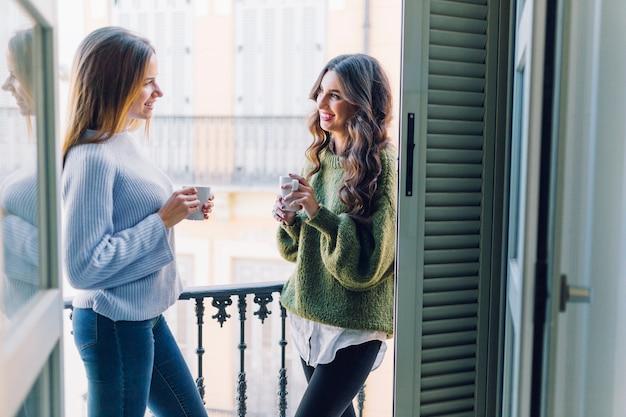 Uśmiechnięte kobiety z kubkami na balkonie