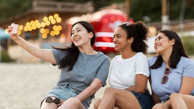 Uśmiechnięte koleżanki siedząc na plaży i biorąc selfie