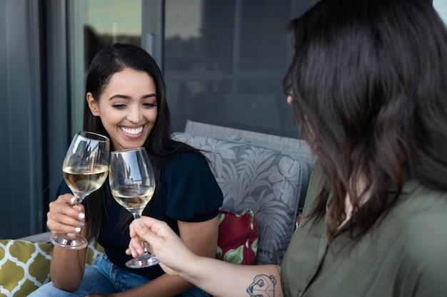 Uśmiechnięte koleżanki spędzające czas razem i pijące wino na tarasie