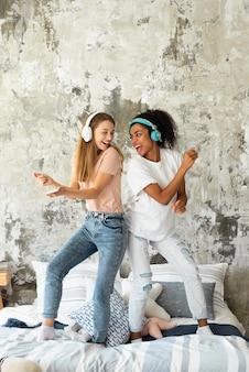 Uśmiechnięte koleżanki tańczą na łóżku podczas słuchania muzyki na słuchawkach