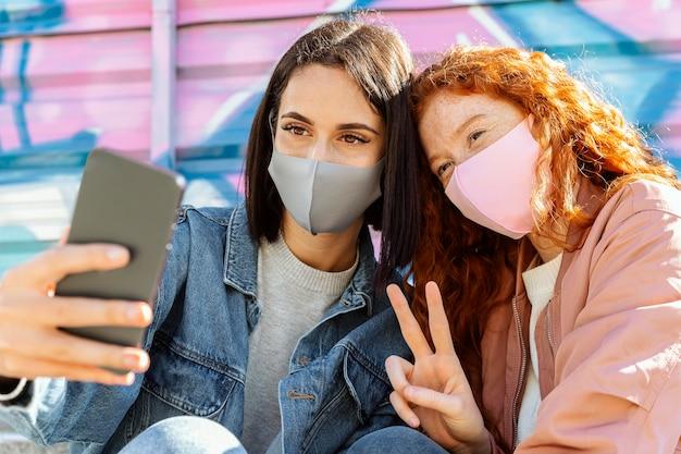 Uśmiechnięte koleżanki z maskami na twarz na zewnątrz przy selfie