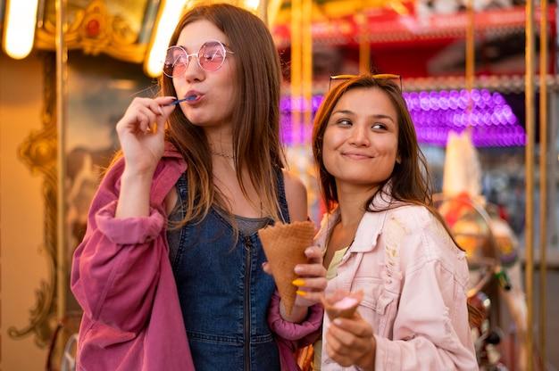 Uśmiechnięte koleżanki z okularami przeciwsłonecznymi w parku rozrywki