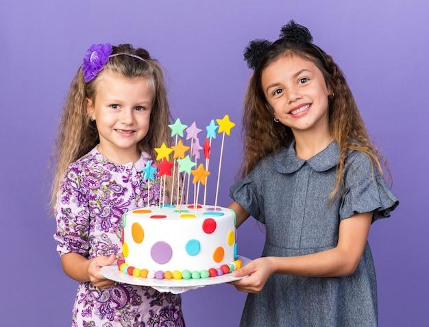 Uśmiechnięte ładne dziewczynki trzymając razem tort urodzinowy na białym tle na fioletowej ścianie z miejsca na kopię