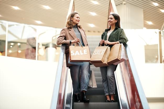 Uśmiechnięte ładne dziewczyny trzymając papierowe torby i schodząc schodami ruchomymi w centrum handlowym