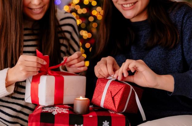 Uśmiechnięte ładne młode dziewczyny otwierają swoje świąteczne pudełka z prezentami siedząc na fotelach i ciesząc się świątecznym czasem w domu