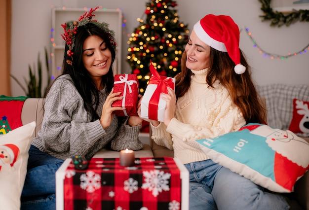 Uśmiechnięte ładne młode dziewczyny w czapce mikołaja i wieńcu ostrokrzewu trzymają i patrzą na swoje pudełka z prezentami siedząc na fotelach i ciesząc się świątecznymi chwilami w domu