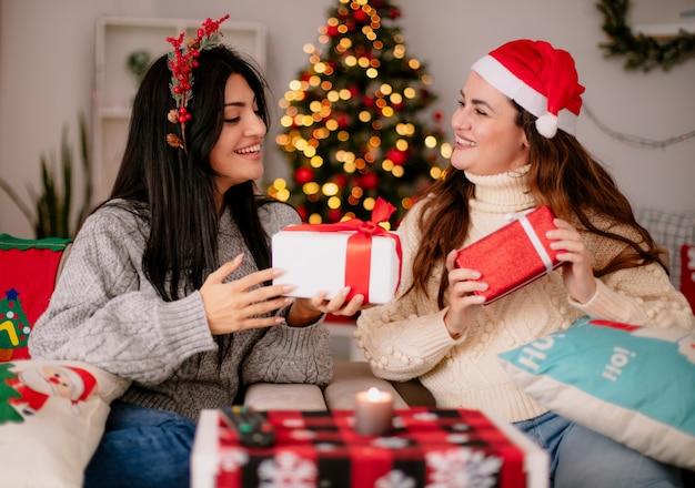 Uśmiechnięte ładne młode dziewczyny w santa hat i holly wieniec trzymają pudełka na prezenty siedząc na fotelach i ciesząc się świątecznym czasem w domu