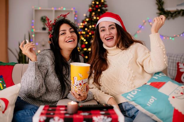 Uśmiechnięte ładne młode dziewczyny w santa hat i holly wieniec trzymają wiadro popcornu siedząc na fotelach i ciesząc się świątecznym czasem w domu