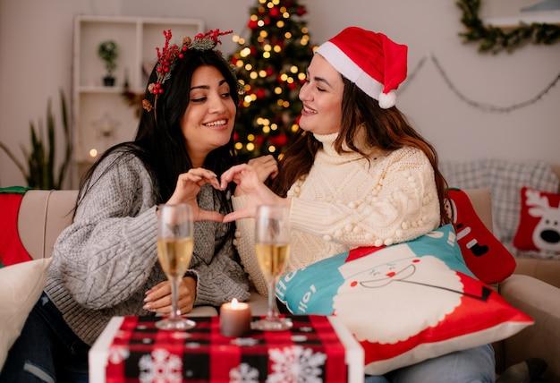 Uśmiechnięte ładne młode dziewczyny z santa hat gestykuluje znak serca razem siedząc na fotelach i ciesząc się świątecznym czasem w domu
