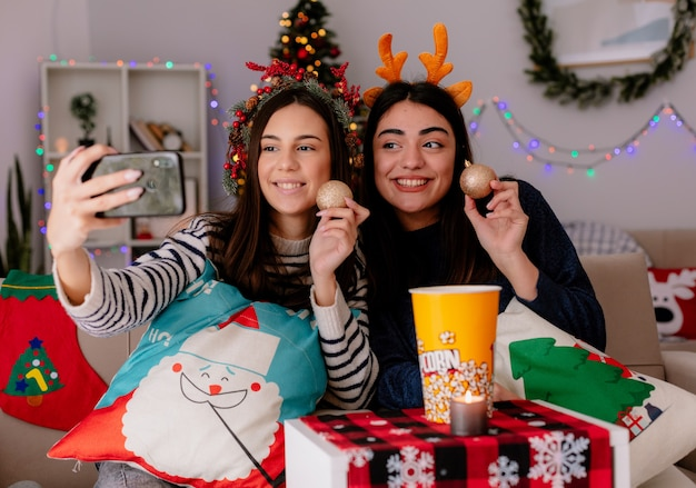 Uśmiechnięte ładne młode dziewczyny z wieńcem ostrokrzewu i opaską renifera trzymają szklane kulki i robią selfie, siedząc na fotelach i ciesząc się świętami w domu